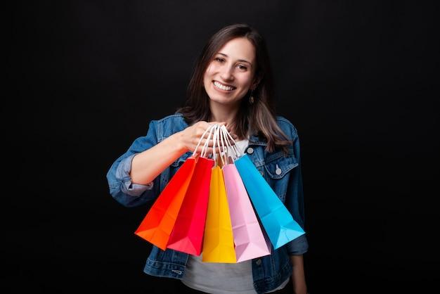 Bella giovane donna che sorride alla macchina fotografica che mostra i suoi sacchi di carta variopinti di acquisto su fondo nero. Foto Premium