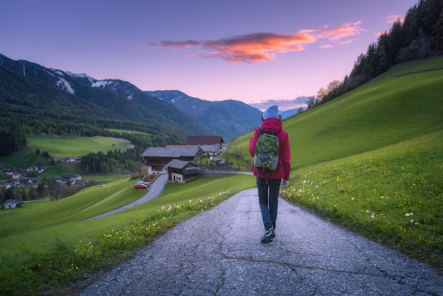 La bella giovane donna con lo zaino sta stando sulla strada della montagna al tramonto in autunno. Foto Premium