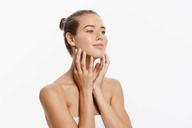 Bellissima giovane donna con la pelle pulita fresca tocco proprio viso. trattamento facciale. Foto Premium