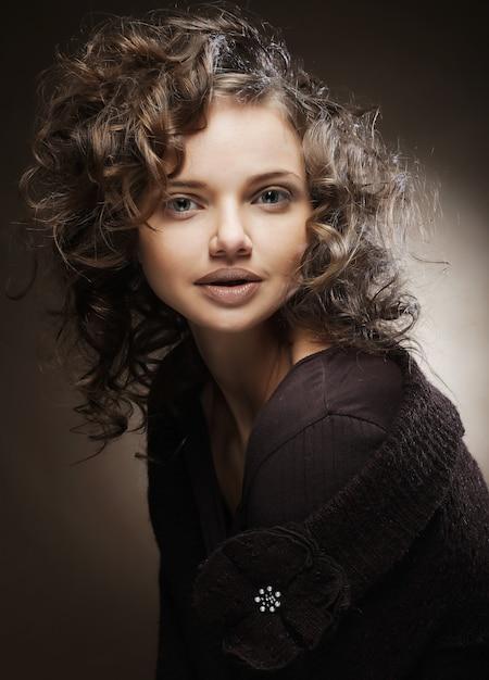 Bella giovane donna con i capelli ricci Foto Premium