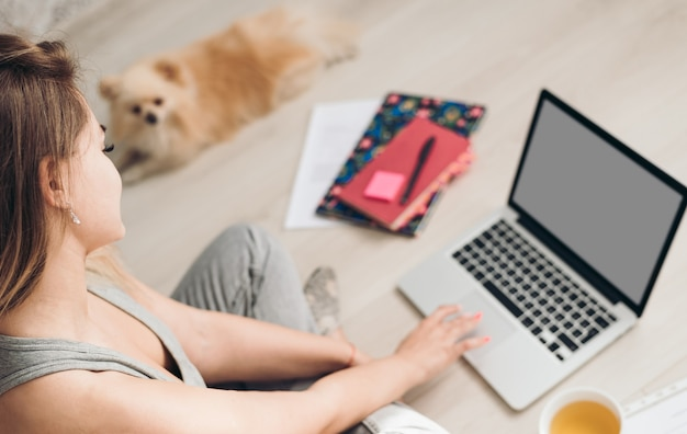 La bella giovane donna lavora da casa. il cane si trova vicino a lei. Foto Premium