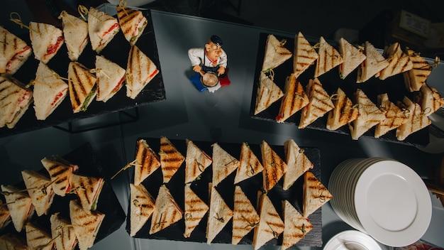 Tabella di banchetto di approvvigionamento meravigliosamente decorata con differenti spuntini e aperitivi dell'alimento con il panino Foto Premium