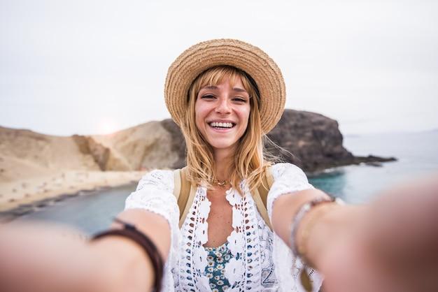 Beautiul giovane donna con cappello prendendo un selfie in spiaggia. Foto Premium