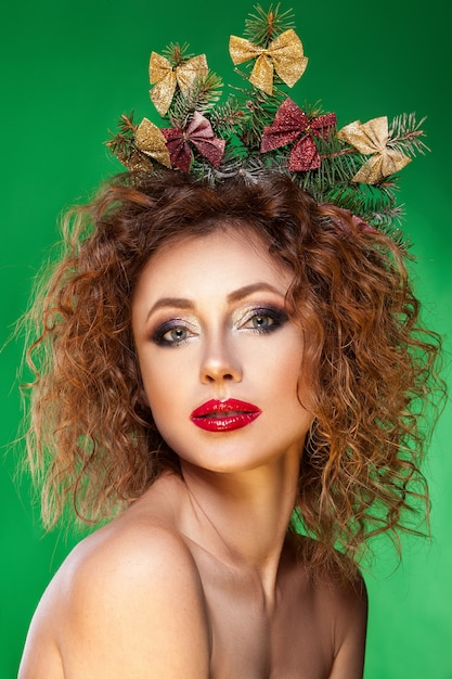 Ragazza di bellezza in un cappello rosso di natale e un albero di abete nelle mani Foto Premium