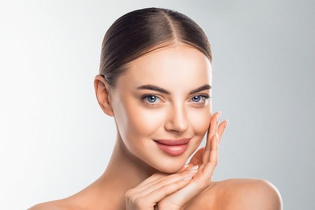 Ritratto del viso di ragazza modello di bellezza. la bella donna che tocca il fronte gode della pelle perfetta Foto Premium