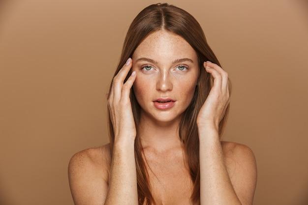 Ritratto di bellezza di una sensuale giovane donna in topless con lunghi capelli rossi in posa, tenendosi per mano sul viso isolato sopra il muro beige Foto Premium
