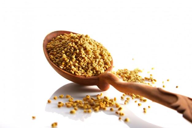 Granuli di polline d'api in un cucchiaio di legno su uno sfondo bianco Foto Premium