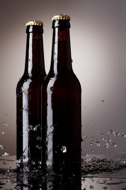 Bottiglie di birra con spruzzi d'acqua Foto Premium