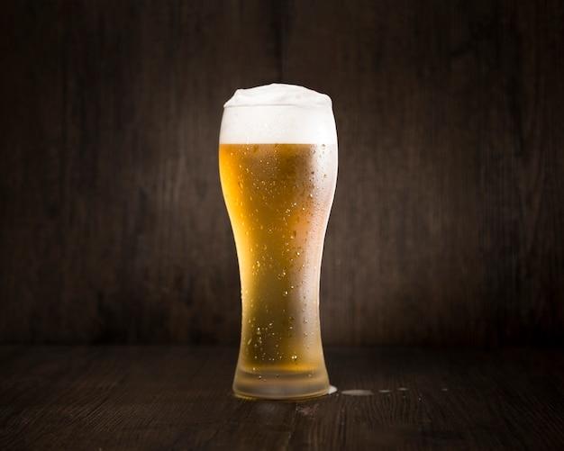 Bicchiere di birra davanti a sfondo nero Foto Premium