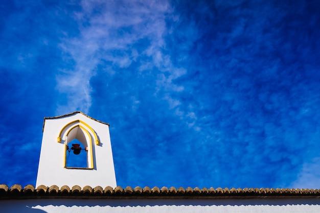 Campanile di una chiesa dalle pareti bianche, sullo sfondo di un bel cielo azzurro. Foto Premium