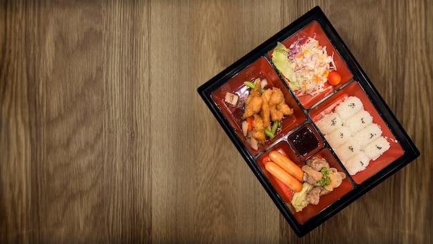 Bento set di carne di maiale pollo e salse tempura cibo giapponese sul ristorante tavolo in legno. Foto Premium