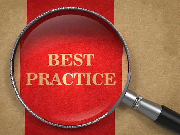 Concetto di migliore pratica. lente d'ingrandimento su carta vecchia con linea verticale rossa. Foto Premium