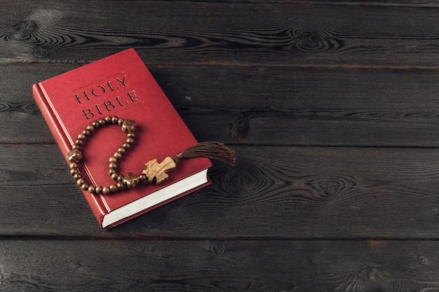 Bibbia e un crocifisso su un vecchio tavolo di legno Foto Premium