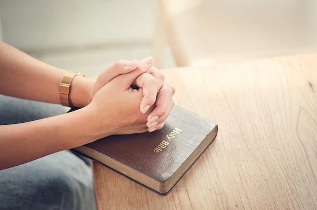 Preghiera biblica piega le mani nella bibbia prega spirituale e religiosa comunica con dio, amore e perdono. Foto Premium