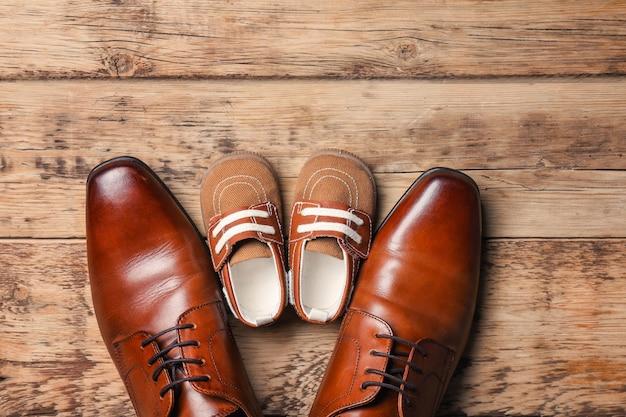 Scarpe grandi e piccole su legno. composizione per la festa del papà Foto Premium