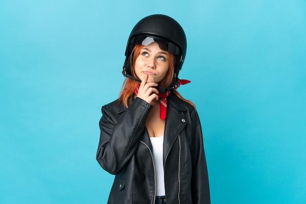 Donna motociclista isolata sull'azzurro che ha dubbi mentre cerca Foto Premium