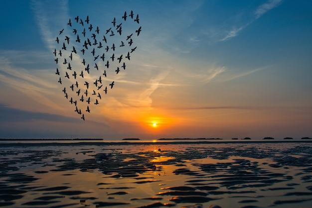 Siluette degli uccelli che volano sopra il mare contro l'alba sotto forma di cuore Foto Premium