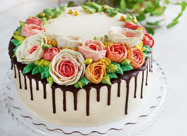 La torta di compleanno con i fiori è aumentato su superficie bianca Foto Premium
