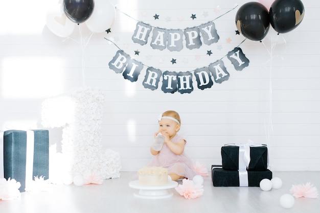 Ragazza di compleanno 1 anno seduta nella zona della foto circondata da regali, fiori Foto Premium