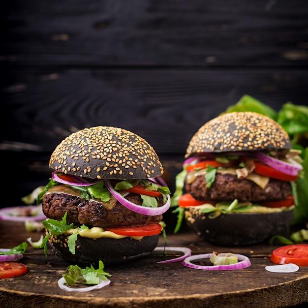 Grande panino nero - hamburger nero con succulenti hamburger di manzo, formaggio, pomodoro e cipolla rossa sulla superficie nera Foto Premium