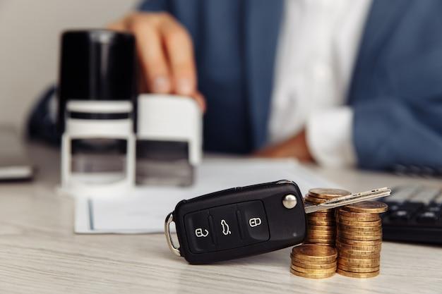 Chiave della macchina nera e timbro su un contratto di vendita di auto firmato. Foto Premium