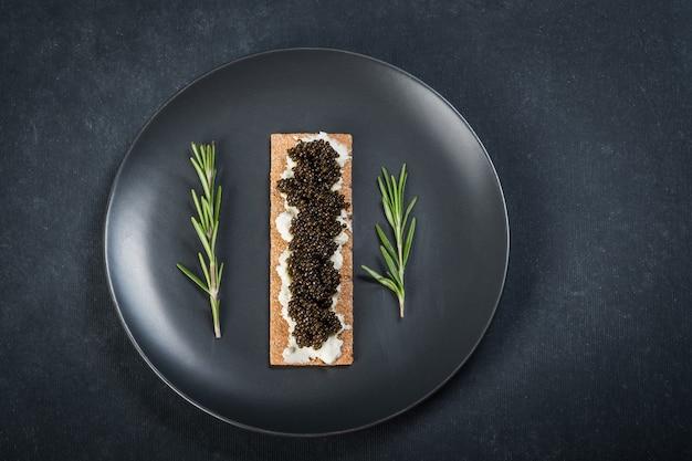 Caviale nero di storione nei biscotti con crema di formaggio. cucchiaio con caviale. piatto rotondo blu. superficie scura Foto Premium