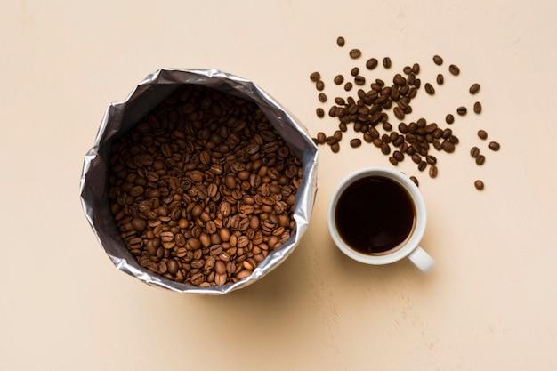 Disposizione dei chicchi di caffè nero su fondo beige con la tazza di caffè Foto Premium