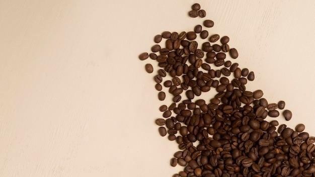 Assortimento dei chicchi di caffè nero su fondo beige con lo spazio della copia Foto Premium