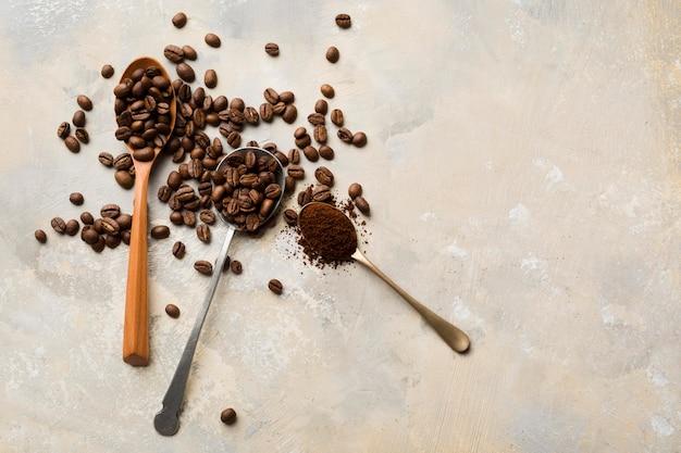 Assortimento dei chicchi di caffè nero su fondo leggero con lo spazio della copia Foto Premium