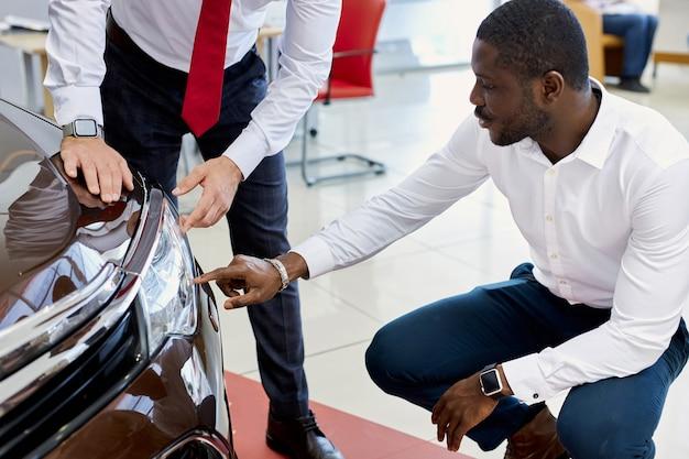 L'uomo nero del cliente fa domande sui fari dell'auto in concessionaria Foto Premium