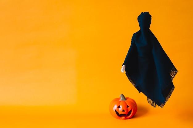 Foglio di fantasma nero che vola su sfondo arancione con zucca sfocata sul pavimento. halloween il concetto minimo. Foto Premium
