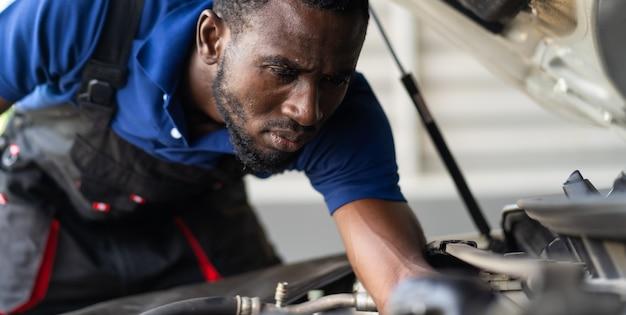 Meccanico maschio nero ripara auto in garage. manutenzione auto e concetto di garage servizio auto. Foto Premium