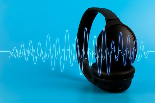 Cuffie musicali nere con onda sonora blu su sfondo blu. concetto multimediale con copia spazio Foto Premium
