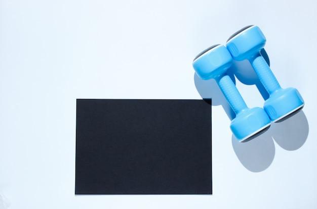 Foglio di carta nero per lo spazio della copia, manubri di plastica su un tavolo grigio. tavolo fitness creativo Foto Premium