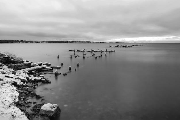 Paesaggio minimalista in bianco e nero con un vecchio molo in rovina nell'artico Foto Premium