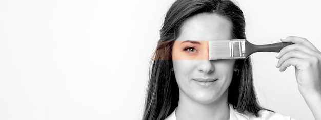 Ritratto in bianco e nero di giovane donna che dipinge il suo occhio in colore giallo con il pennello sul muro bianco Foto Premium