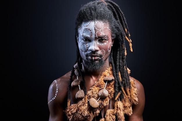 Nero con trucco aborigeno sciamano con fiducia, ragazzo nero isolato in studio. ritratto Foto Premium