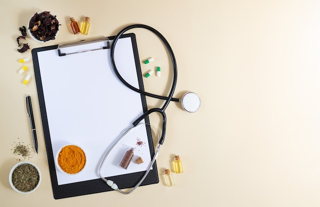 Appunti in bianco con lo stetoscopio, varie erbe sane, spezie, capsule e oli vista dall'alto Foto Premium