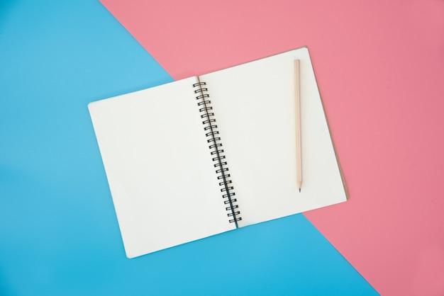 Taccuino in bianco con la matita sul fondo di colore Foto Premium