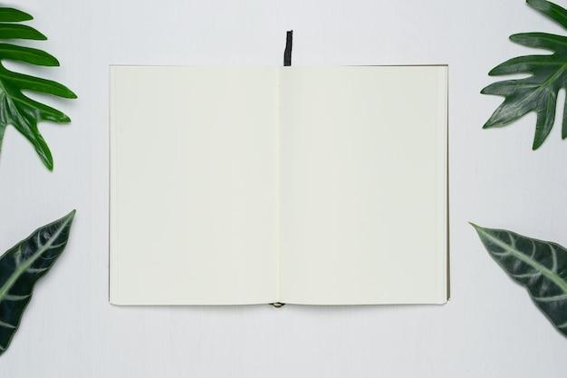 Soppressione la pagina aperta del taccuino sulla scrivania di legno bianca del fondo Foto Premium