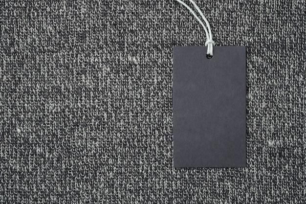 Etichetta o etichetta della carta in bianco sul fondo tricottato dei vestiti della lana Foto Premium