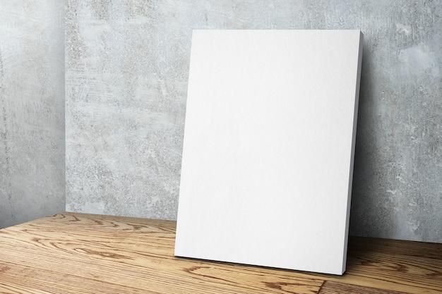 Cornice in tela bianca vuota che si appoggia al muro di cemento e pavimento in legno Foto Premium