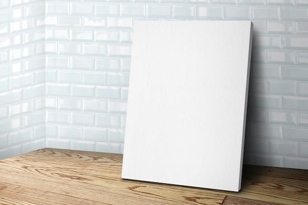Cornice in tela bianca vuota che si appoggia al muro di piastrelle e pavimento in legno Foto Premium