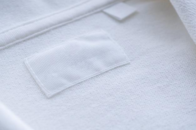 Etichetta di vestiti bianchi in bianco sulla nuova camicia Foto Premium
