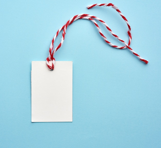 Etichetta in bianco del libro bianco con la corda bianco-rossa su un fondo blu Foto Premium