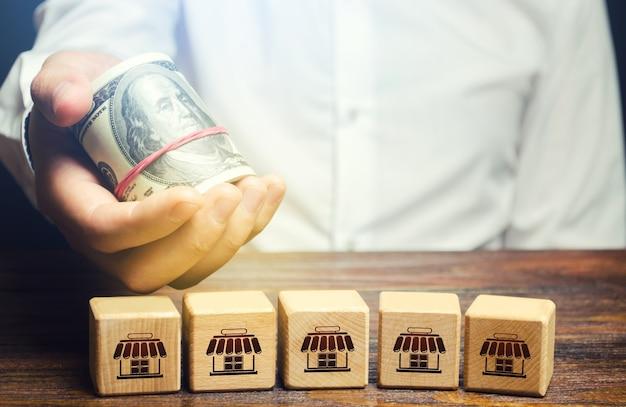 I blocchi che simboleggiano la rete aziendale e l'uomo d'affari porge i soldi. offerta di acquisto Foto Premium