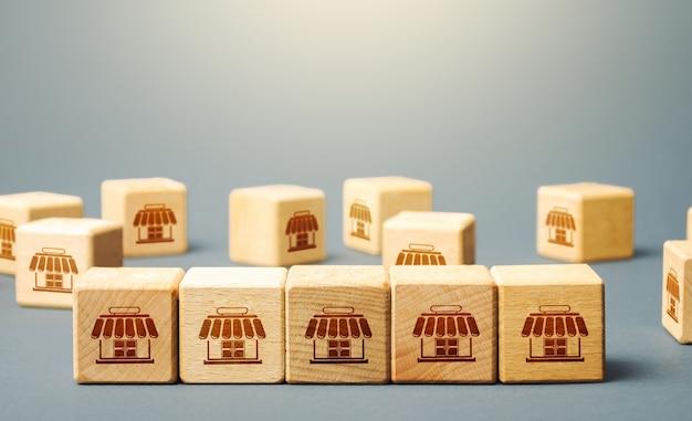 Blocchi che simboleggiano negozi per lo shopping. costruire un impero commerciale di successo. concetto di franchising Foto Premium