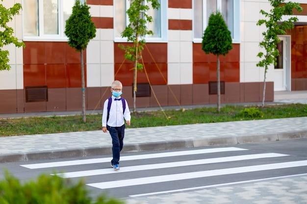 Uno scolaro biondo con gli occhiali e uno zaino va a scuola su un passaggio pedonale Foto Premium
