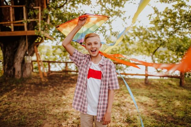 Ragazzo teenager biondo con l'aquilone variopinto Foto Premium