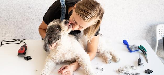 Donna bionda che cura un cane a casa Foto Premium